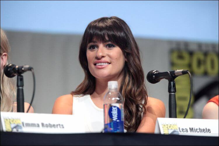 Portrait of Lea Michele, sitting at a desk for an interview with a name tag and a microphone placed in front of her