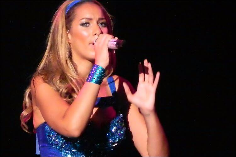Leona Lewis singing, shot from an angle, wearing a blue dress, bracelet and headband