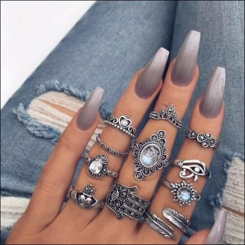 Woman's white hand with lots of rings and an ombre gray nail design