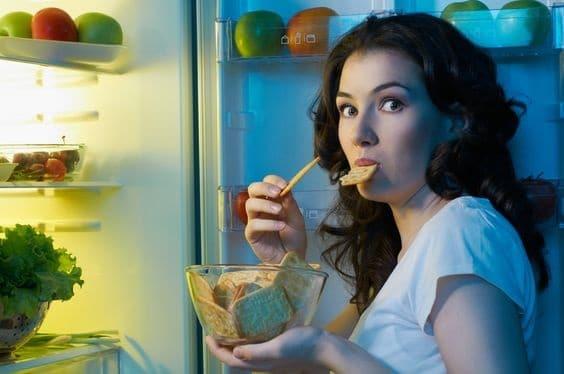 Girl snacking at night from the fridge