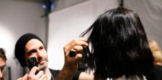 Hairstylist styling a model's hair before the show