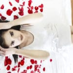 Woman in bed surrounded by rose petals, ready for Valentine's Day