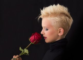 Woman with short hair smelling a rose
