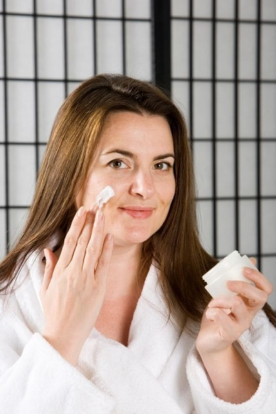 Woman puting on face cream
