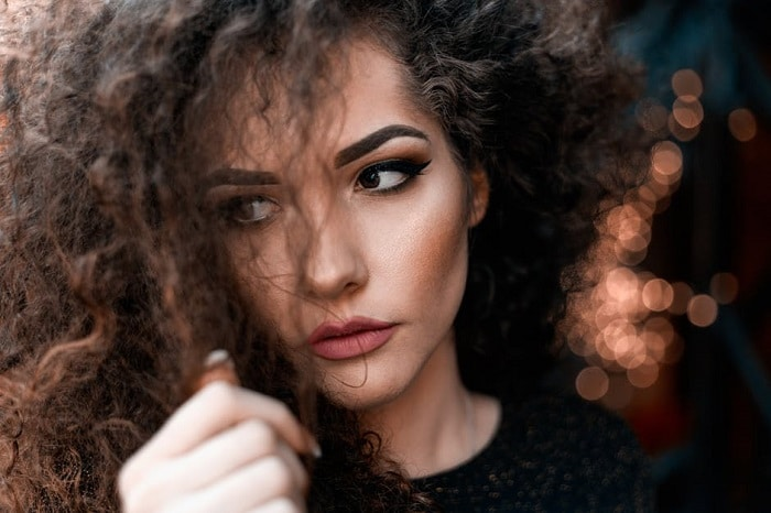 close up on the face of a curly hired woman looking to the left