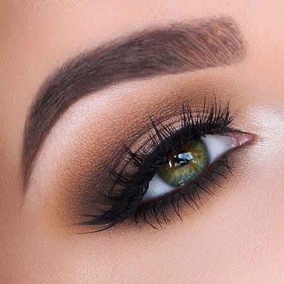 close up on green eye and eyebrow with brown makeup on