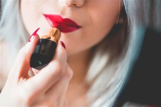 Girl applying red lipstick
