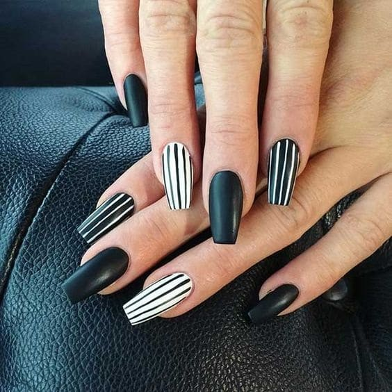 hands with black and white striped manicure