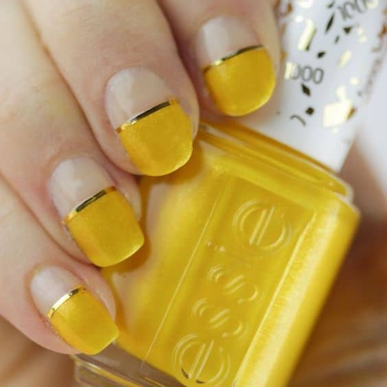 hand with half yellow nails holding yellow nail polish bottle
