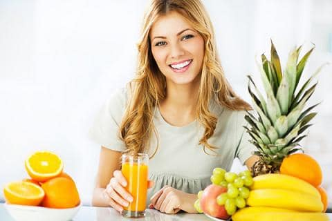 woman surrounded by fruits and a juice