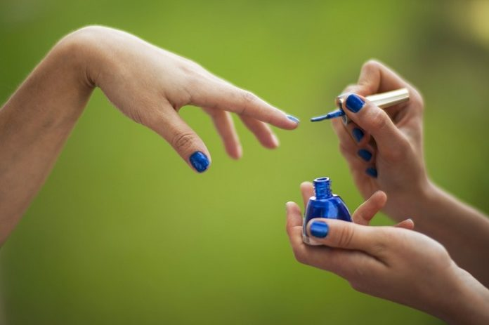 someone painting their nails blue