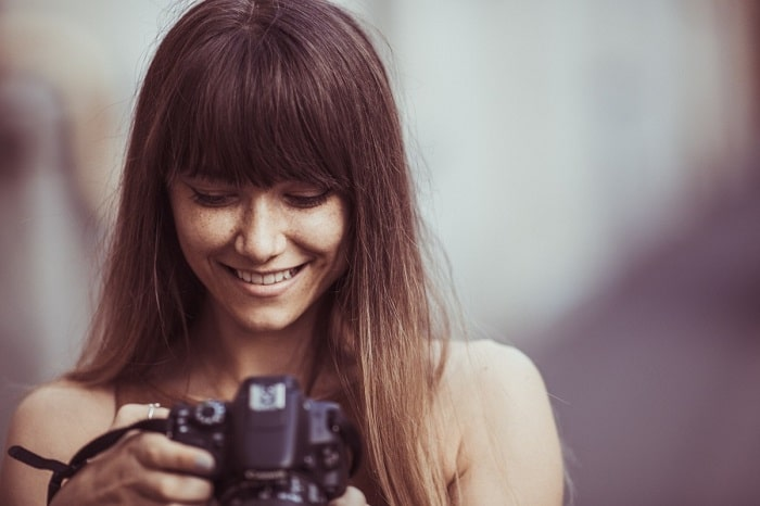 girl with bangs taking a photo