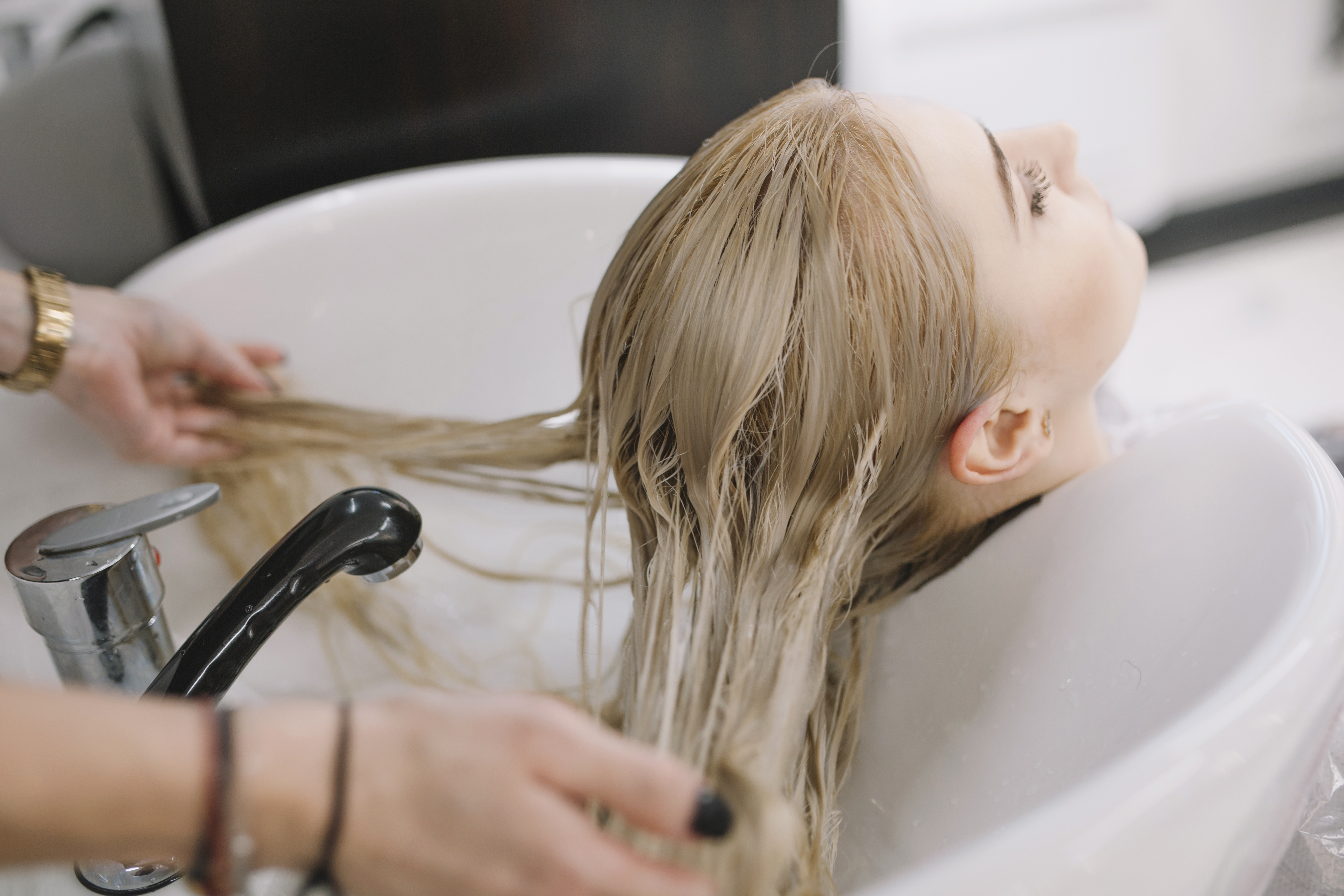 hairdresser washing client hair with ketoconazole shampoo