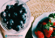 blue berries and straw berries in glass bowls