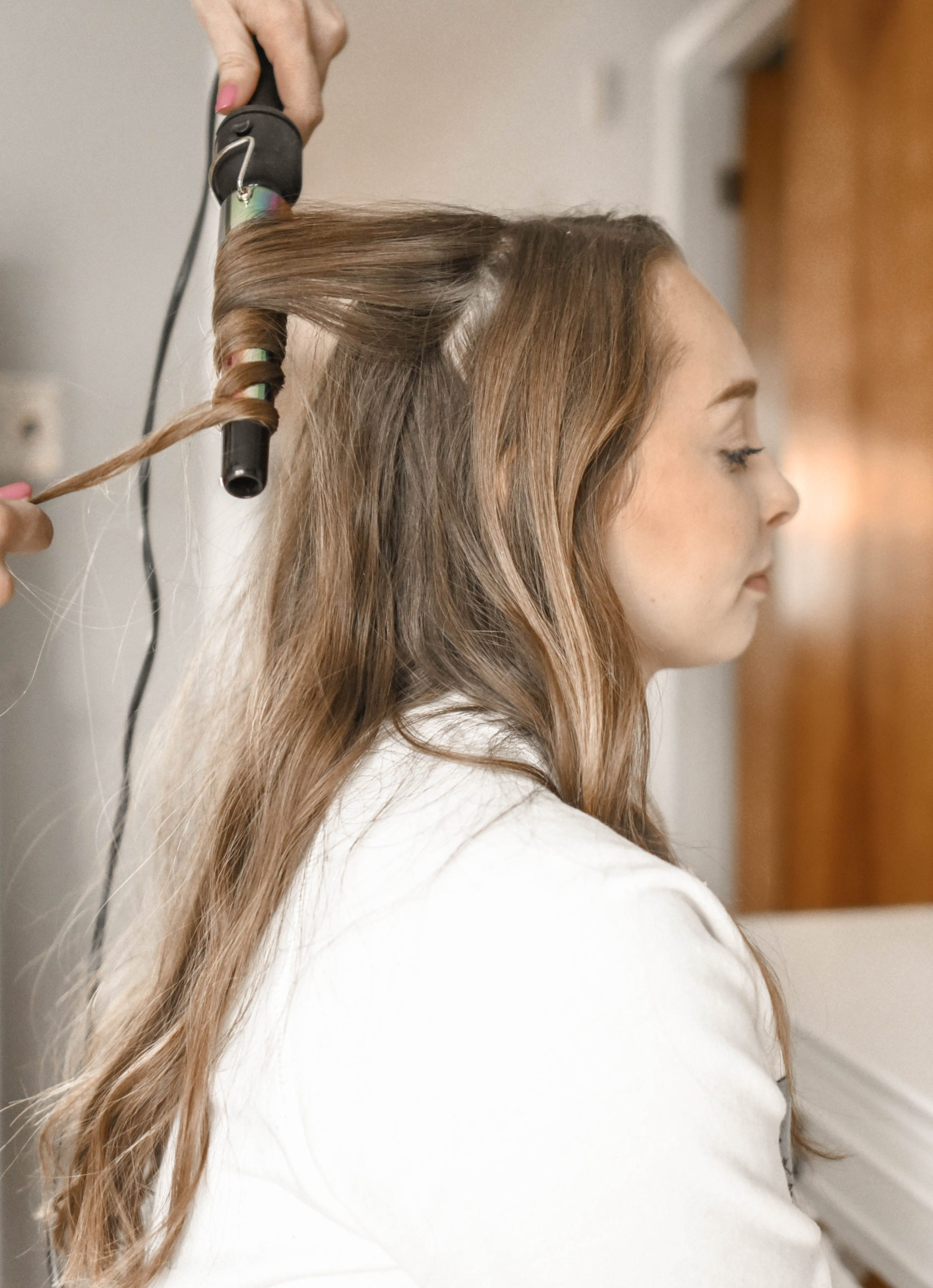 A person is curling the hair of the blonde woman sitting in front of a mirror