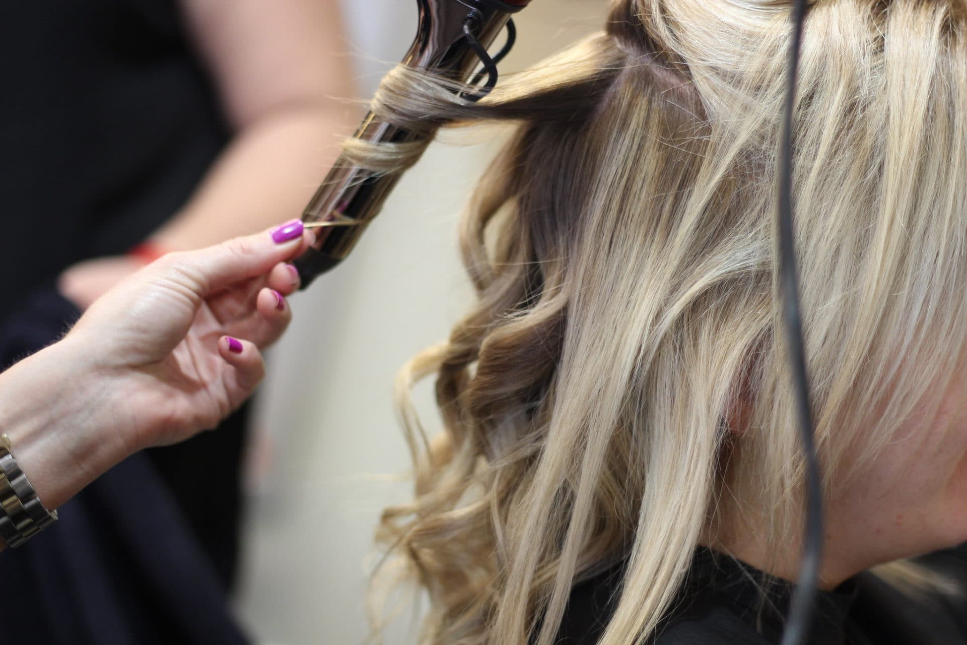 A person is curling the blonde hair of a woman